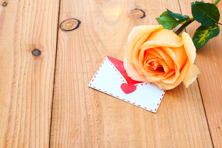 orange rose: orange rose and valentine card on wood table