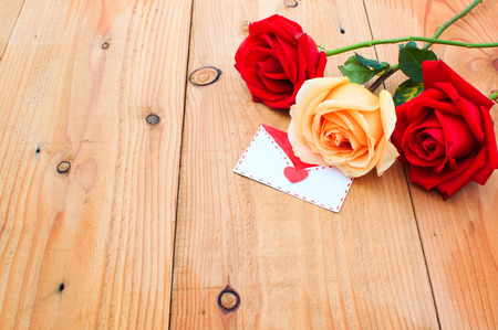 orange roses: Red and orange roses flowers and valentine card on wood table Stock Photo