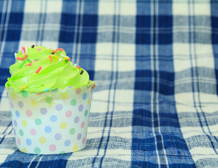 picnic tablecloth: Green Cupcake with colorful candy on blue picnic tablecloth