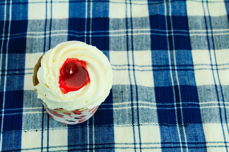 picnic tablecloth: Cupcakes with buttercream frosting and strawberry jam on blue picnic tablecloth