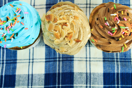 picnic tablecloth: colorful cupcakes with colorful candy on blue picnic tablecloth Stock Photo