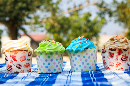 picnic tablecloth: colorful cupcakes with colorful candy on blue picnic tablecloth in garden.