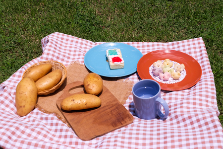 Picnic for a summer vacation with potato , snack and cake.