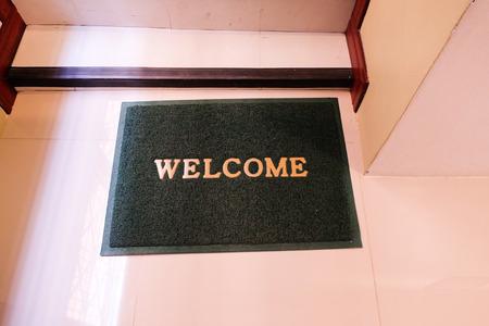 green welcome carpet on floor.