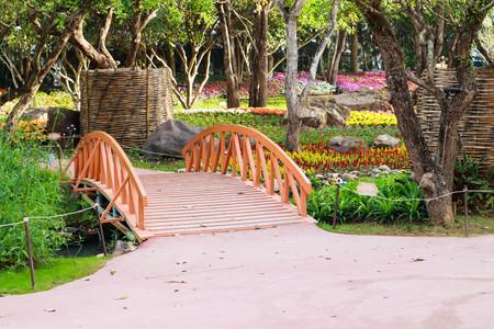 Wood bridge in flower garden. Stok Fotoğraf