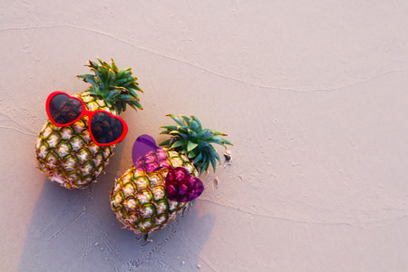 Couple of pineapples in sunglasses on the sand . Tropical summer vacation concept.
