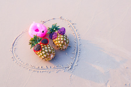 Couple of pineapples in Trendy Sunglasses on Beach.