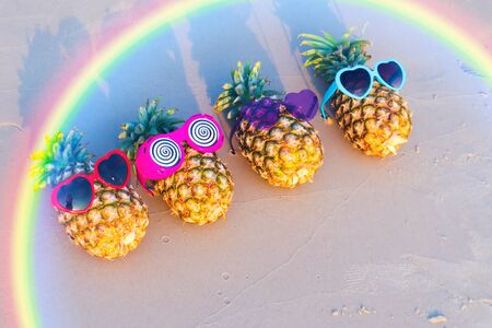 Family of funny attractive pineapples in sunglasses on the sand ,Tropical summer vacation concept.