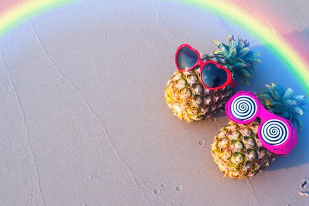 Couple of pineapples in funny sunglasses on the sand .