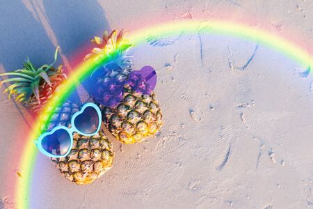 Couple of pineapples in funny sunglasses on the sand in sunset. Tropical summer vacation concept.