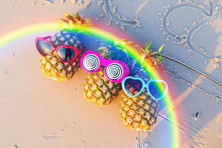 Friend of pineapples in funny sunglasses on the sand. Stockfoto