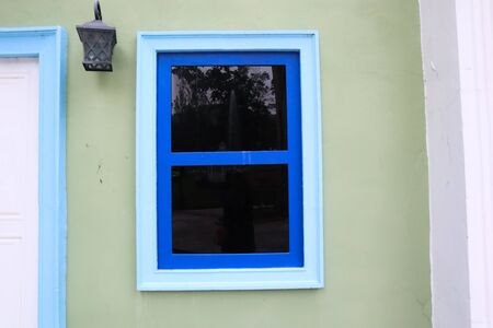 Blue window glass on green wall of house.
