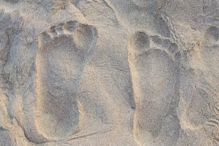 Footprints of a womens feet on the sand.