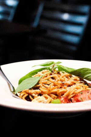 Stir-Fried Spaghetti With Dried Chili And sausage White plate on wood table.