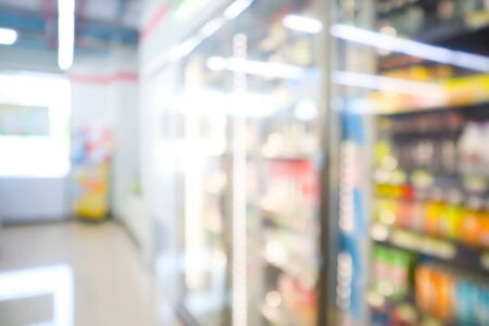 Blur image of Many drinks bottles sale on the shelf in a supermarket.