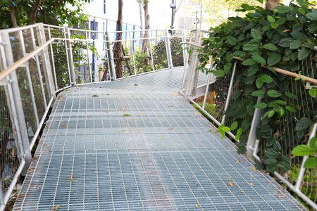 Narrow pedestrian walkway made of metal in the form of a bridge in garden.