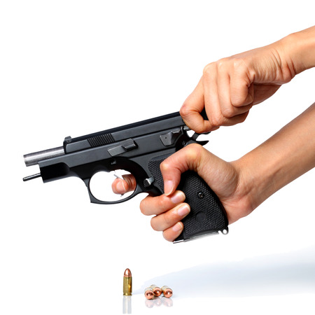 A close up of a pair of hands cocking a black handgun. The bullet can be seen inside the gun..