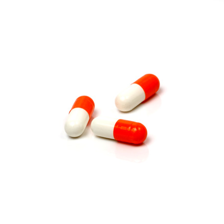 Red capsules on white background. Clipping path included