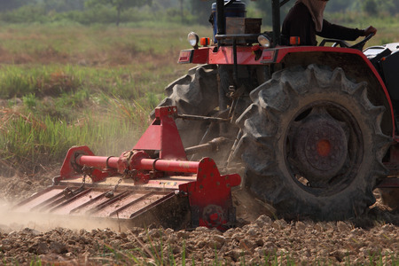 Red tractor plows field at high speed  Stock Photo