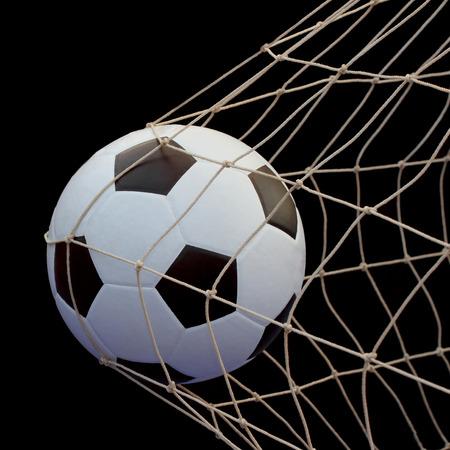 balon de futbol: El balón de fútbol volando en la red aislada sobre fondo Negro Foto de archivo