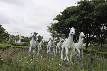 Many horse statues on the field.