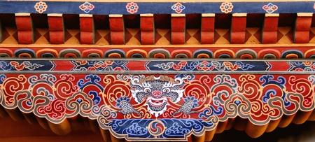 tibetan house: Colorful Bhutanese art of Tibetan dragon painted on wood at the entrance of house at Paro, Bhutan
