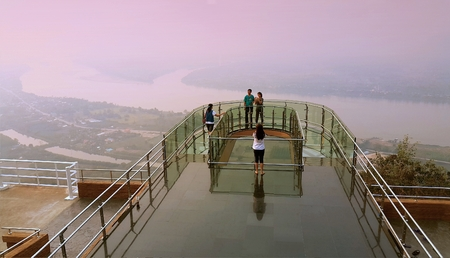 Nong Khai province, Thailand- April 28,2016: Tourists walking and taking photograph on transparent  sky walk to see view of Mekong River during sunset at Wat Pha Tak Suea, Sangkhom district,  Nong Khai province, Thailand. Editorial