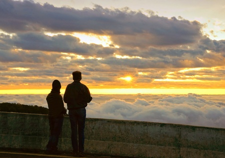 Silhouette couple looking at the beautiful sunrise on the top of mountain with the view into misty valley. Morning mountain landscape with wave of fog, Doi Inthanon National Park, Chiang Mai, Thailand