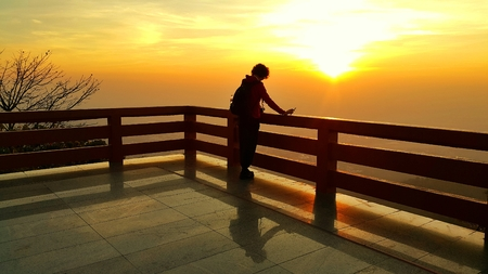 Silhouette of a short curly hair asian woman looking at dramatic sunrise landscape in the morning  at view point balcony of Wat Pra That Doi Suthep, Chiang Mai, Thailand Stock Photo