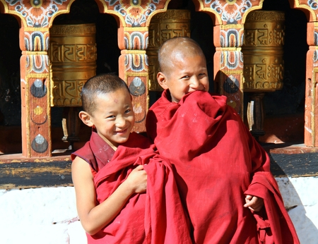 PARO, BHUTAN - NOVEMBER06,2012 : Unidentified smiling young monks standing by the religious prayer wheels at Paro Rinpung dzong, Paro, Bhutan Editorial