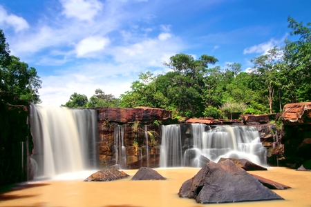 Turbid water stream in early rainy season at Tat Ton Waterfall during sunny day with blue sky, Tat Ton National park, Chaiyaphum province, Thailand Stock Photo