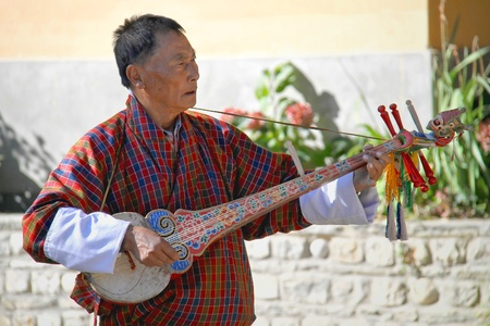 religious clothing: PARO, BHUTAN - November10, 2012 : Unidentified old man musician in traditional dress (Gho) playing Dramnyen instrument at hotel in Paro, Bhutan