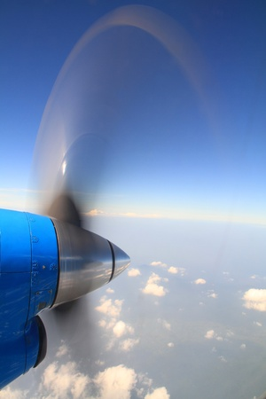 Propeller of old airplane with view of beautiful white cloud as seen through window of an aircraft