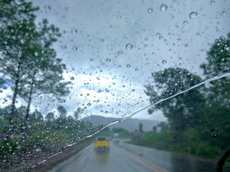 Raindrops on the windshield cause poor visualization and dangerous driving during rainy and slippery road.View from car seat.