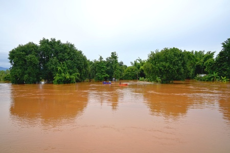 Flash flood by red turbid water flows down from the mountain due to torrential rain with people paddling boats in Phitsanulok, Thailand