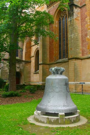 A church bell in the grass outside the Cathedral in LuxembourgCity