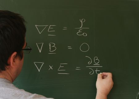A teacher writing Maxwells equations on a chalkboard photo