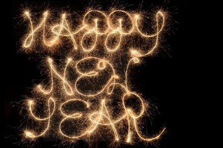 Happy New Year written with sparklers in the sky