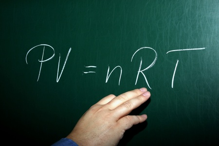A Teacher Writing The Ideal Gas Law on a Chalkboard