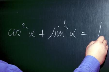 Teacher Writing an Equation on a Chalkboard photo