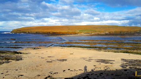 A view of the Brough of Birsay in Orkney, UK with photographers shadow in bottom corner