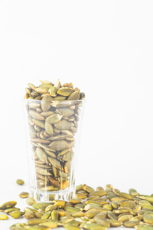 Pumpkin seeds close up in glass on white blackgroud photo