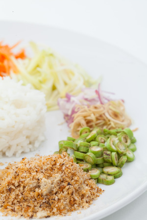 Nasi kerabu or kao yum, Southen Thai-Style rice with herbs and vegetables on white paper background photo