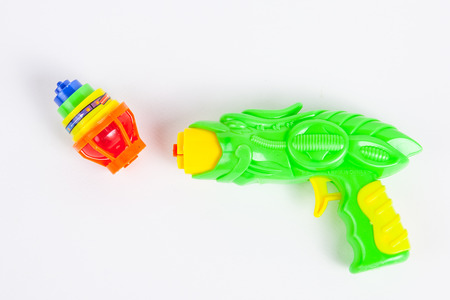toy gun with spinning top on white paper background Imagens