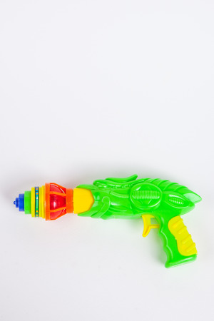 Toy gun with spinning top on white paper  Imagens