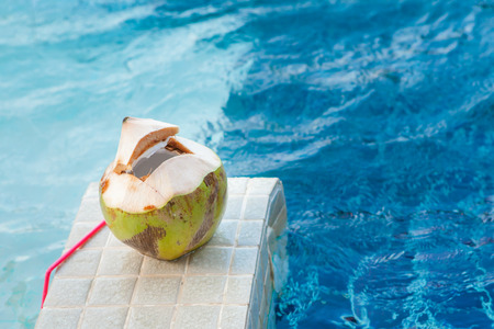 fruit water: Coconut with straws to drink on the side of the pool Stock Photo