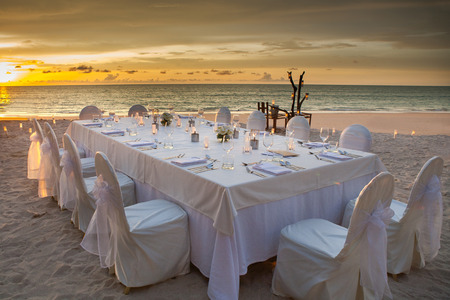 dining table and chairs: long dinner table on the beach at Thailand