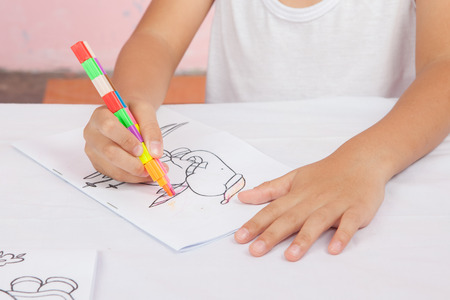 assign: Asian boy Sitting coloring homework teachers assign.