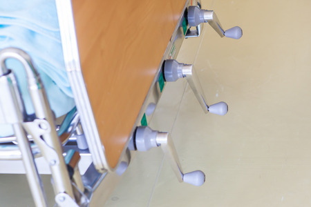 surgery stretcher: The adjustable patient beds in hospital room.