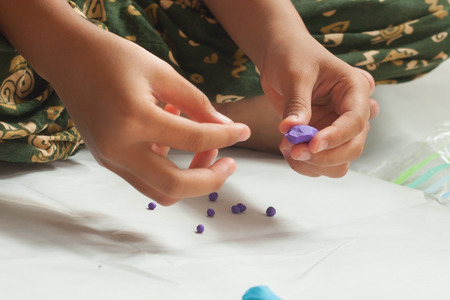 modelling clay: Child hands with plasticine in home at Thailand. Stock Photo